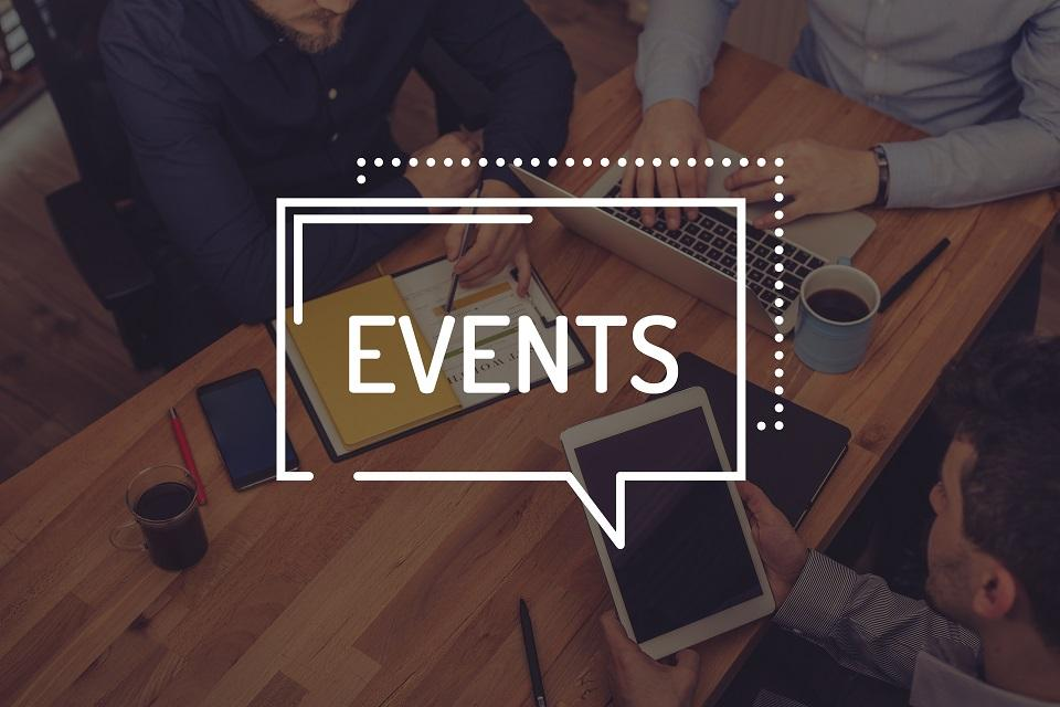 Events written on top of a group of people sitting around a table on electronic devices
